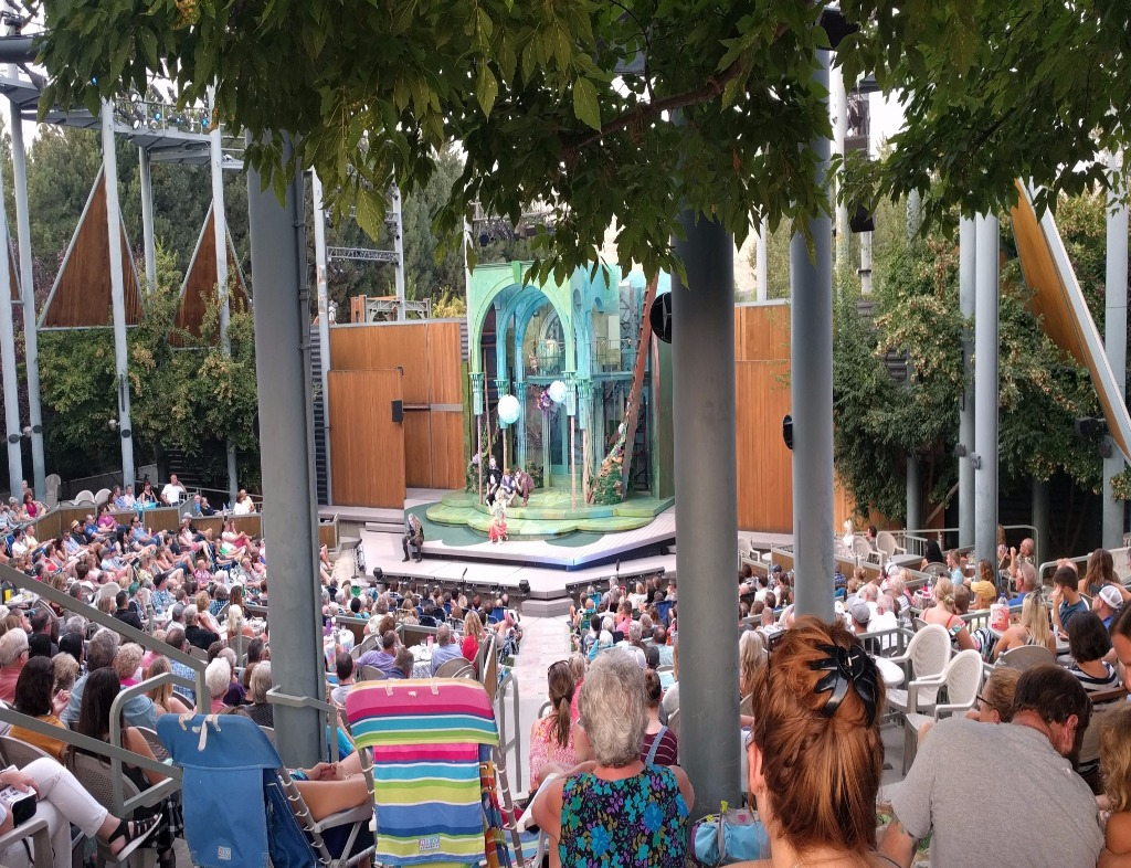 The beginning of A Midsummer Night's Dream at the Idaho Shakespeare Festival. An outdoor venue, but intimate. The photo was taken from the back of the lawn, which overlooks an audience with blankets and clothes of many bright colors. There is a tree under which one sees the stage. Green floor and wood sides. The scenery is a barebones with a few arches.