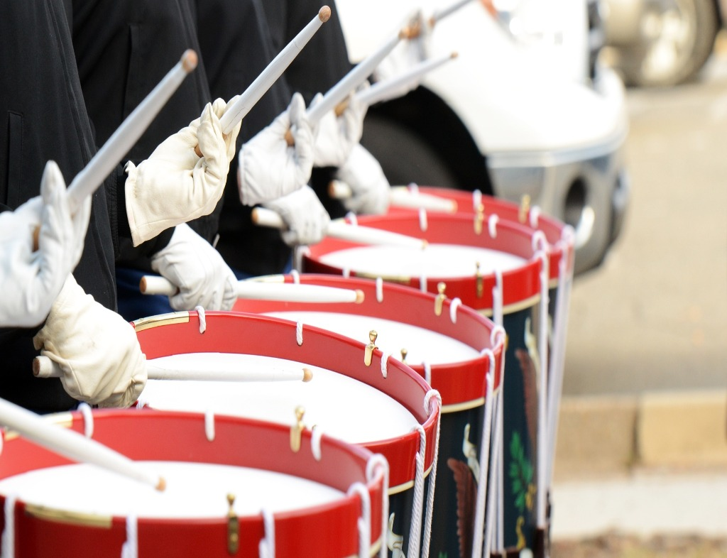 A line of five field drums being played be musicians with white gloves, white drumsticks, and black or dark blue outifts. The drumheads are white, the drums are red at the rim and have a black or dark blue body.
