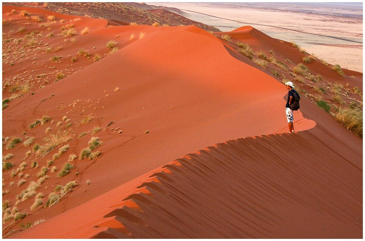 Standing on blood red sand dunes in Namibia