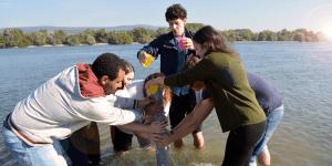 Menschen lösen Teamaufgabe im Fluß
