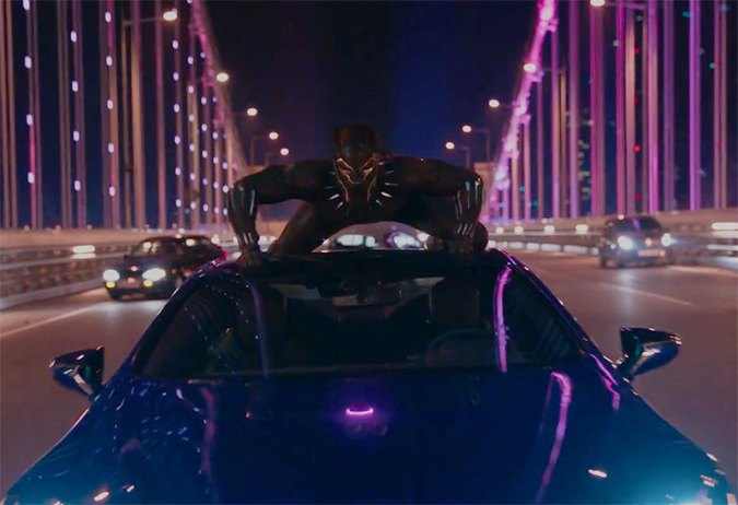 Black Panther crouched on top of a moving vehicle driving over a bridge at night.