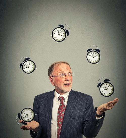 A man is juggling 5 small clocks