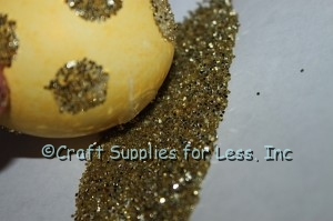 Roll yellow egg with glue dots in gold glitter