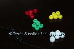 String 5 black pony beads onto elastic cord.