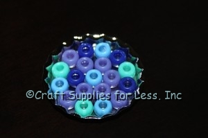 Assorted Pony Beads arranged in Large Metal Bottle Cap