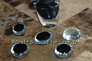 Back of clear glass gems painted with black nail polish