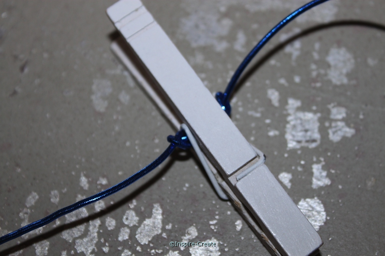 Tie Elastic Cord on each side of white clothespin to hold in place on banner