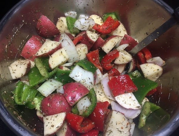 chopped peppers, potatoes, and onions in a stainless steel bowl with seasonings