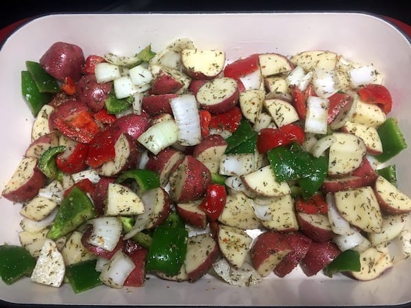 chopped potatoes, peppers, and onion in roasting pan ready to go in the oven