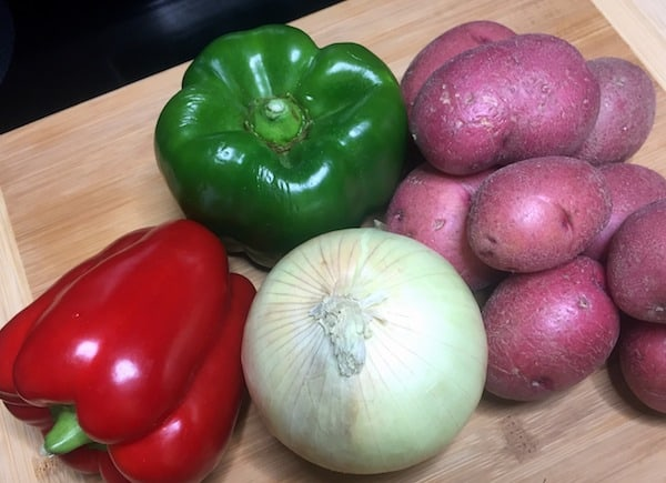 whole potatoes, red and green peppers, and onion on a wood cutting board