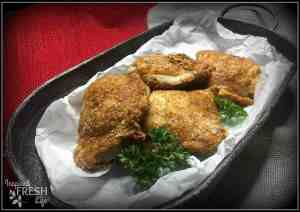 crispy oven-roasted chicken thighs on parchment paper on a tin platter garnished with parsley
