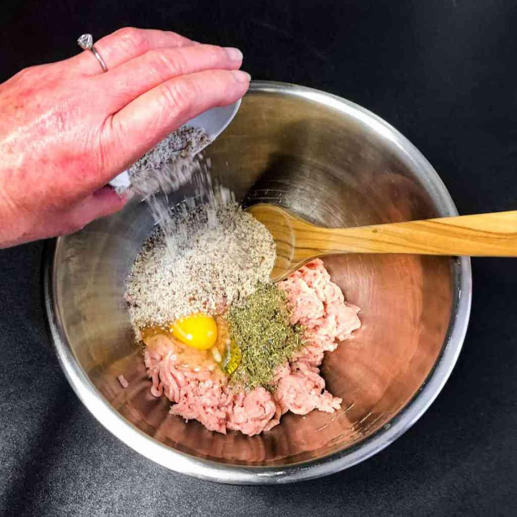 Hand adding almond meal to the meatball ingredients in a stainless steel bowl.