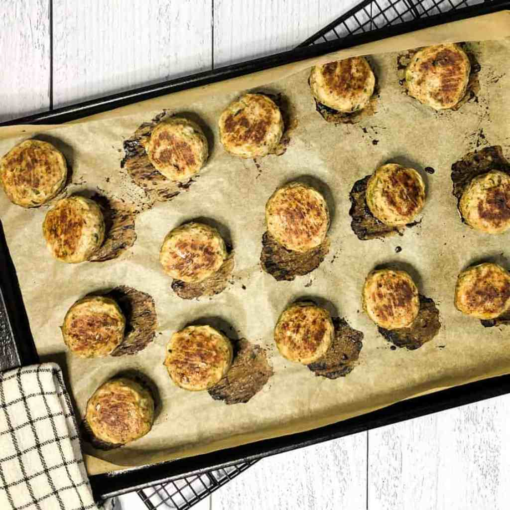 Baked meatballs on a sheet tray lined with parchment paper.