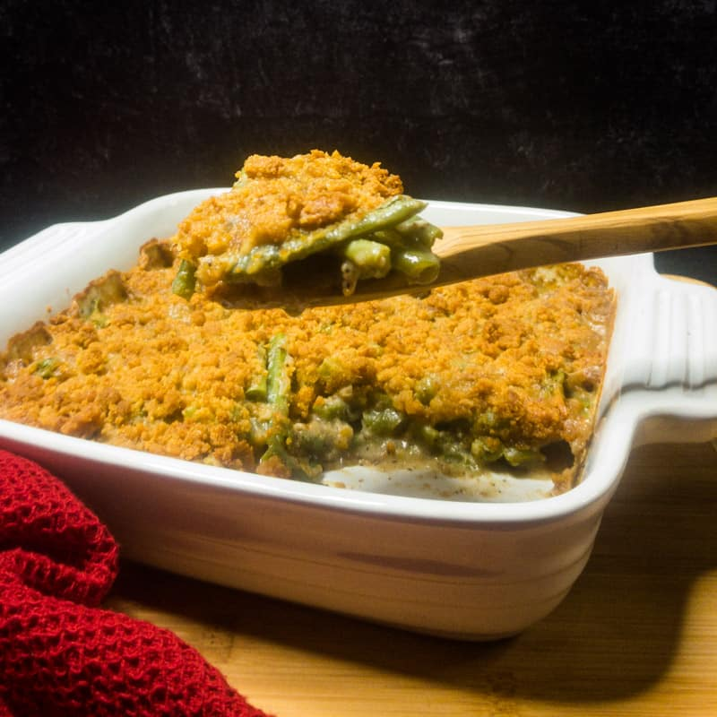 Green Bean Casserole in a white dish on top of a brown cutting board with a spoon holding a scoop.