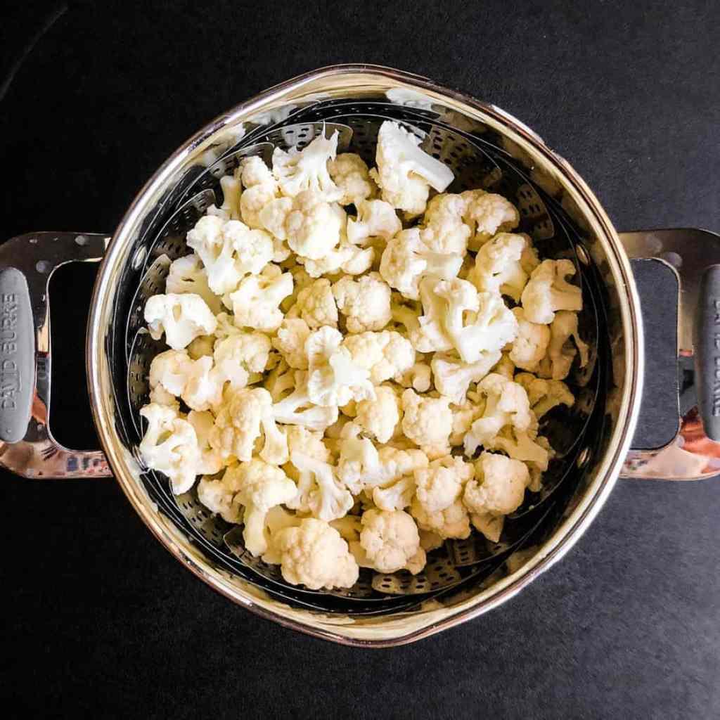 Cut cauliflower in a steamer basket.