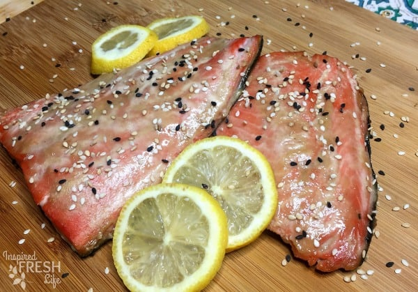 Miso Ginger Cedar Plank Salmon garnished with lemon wheels and sesame seeds.