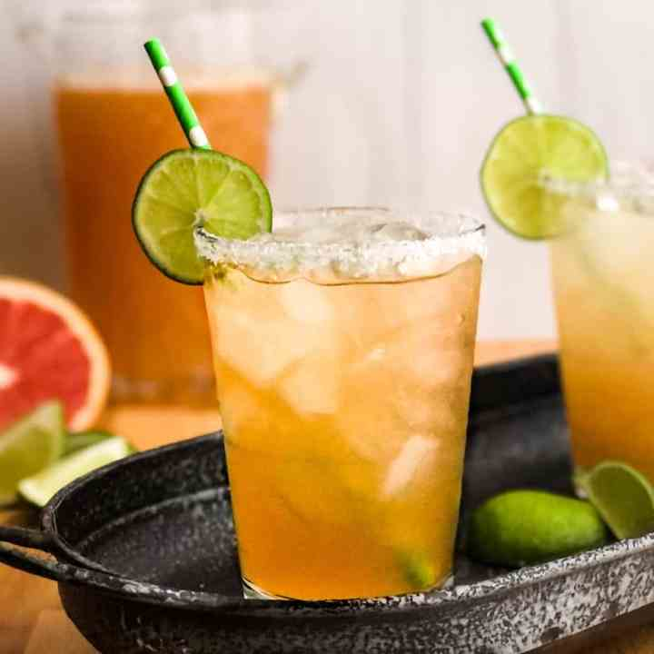 Closeup of a Paloma cocktail with a salted rim, garnished with lime while with a pitcher of Palomas blurred in the background.