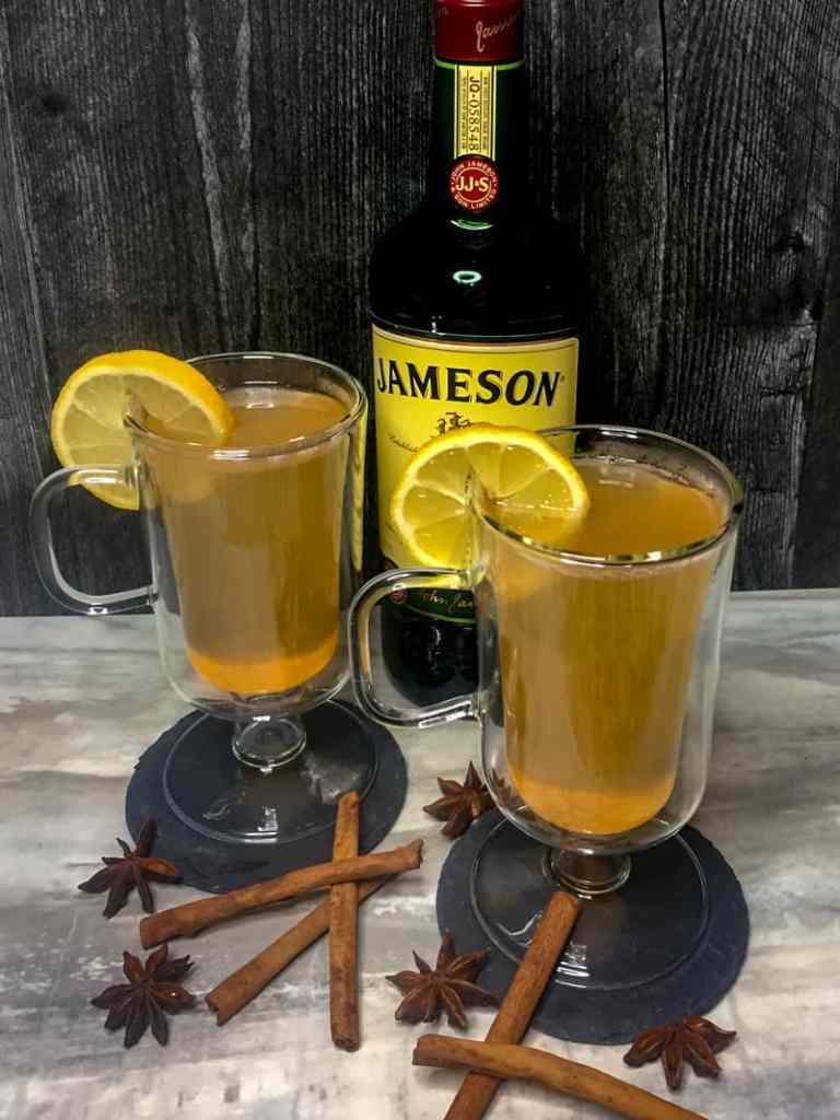 Spiced Hot Toddy in glass mugs with a lemon garnish in front of a bottle of Jameson whiskey