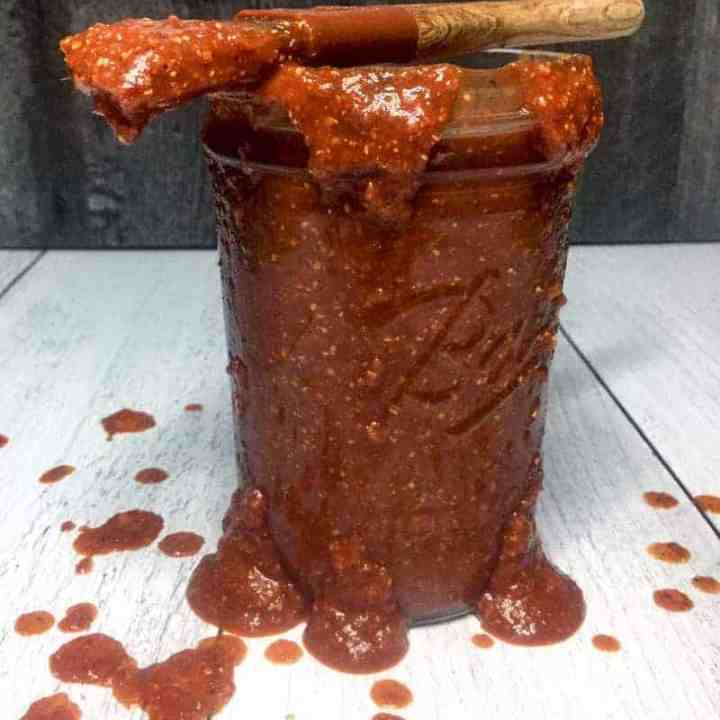 Jar of Homemade Barbecue Sauce on light background with a basting brush on top, surrounded by drips of sauce