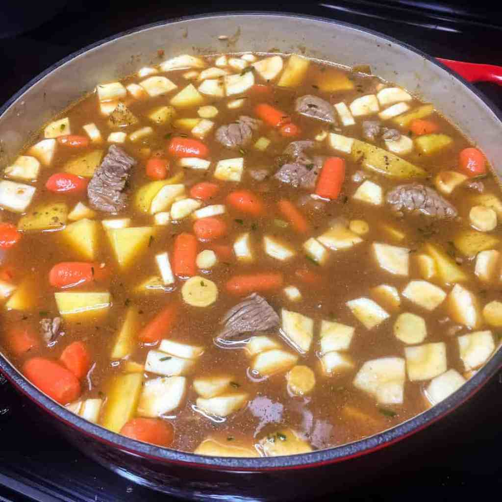 Beef broth, meat, and root vegetables added to the Dutch oven.