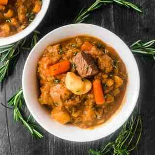 Close up overhead shot of Irish Beef Stew in a white bowl garnished with rosemary and thyme.