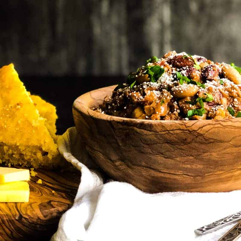 Chorizo and Bean Chili in a wood bowl with cornbread and butter on the side