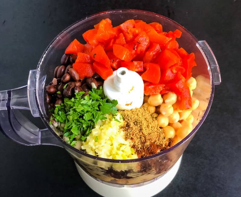 All the ingredients for Chipotle Black Bean Hummus in a food processor ready to be blended.