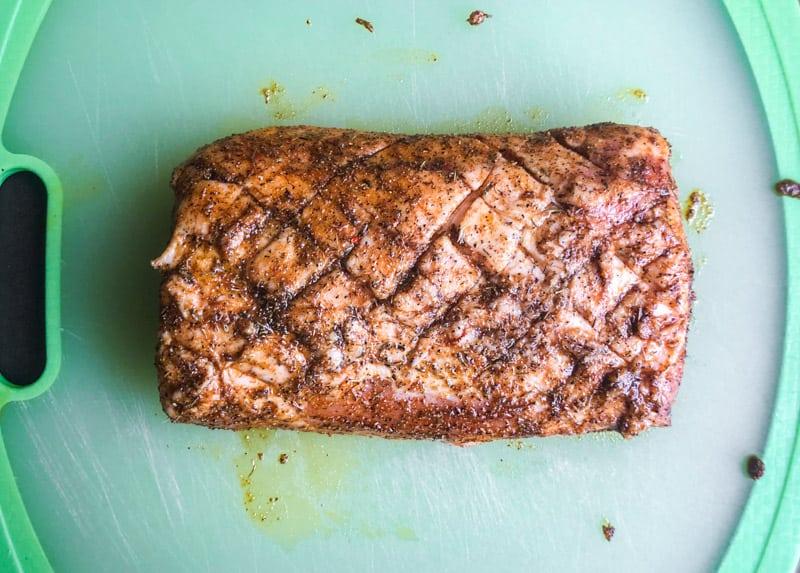 Wet rub on pork loin on a green cutting board.