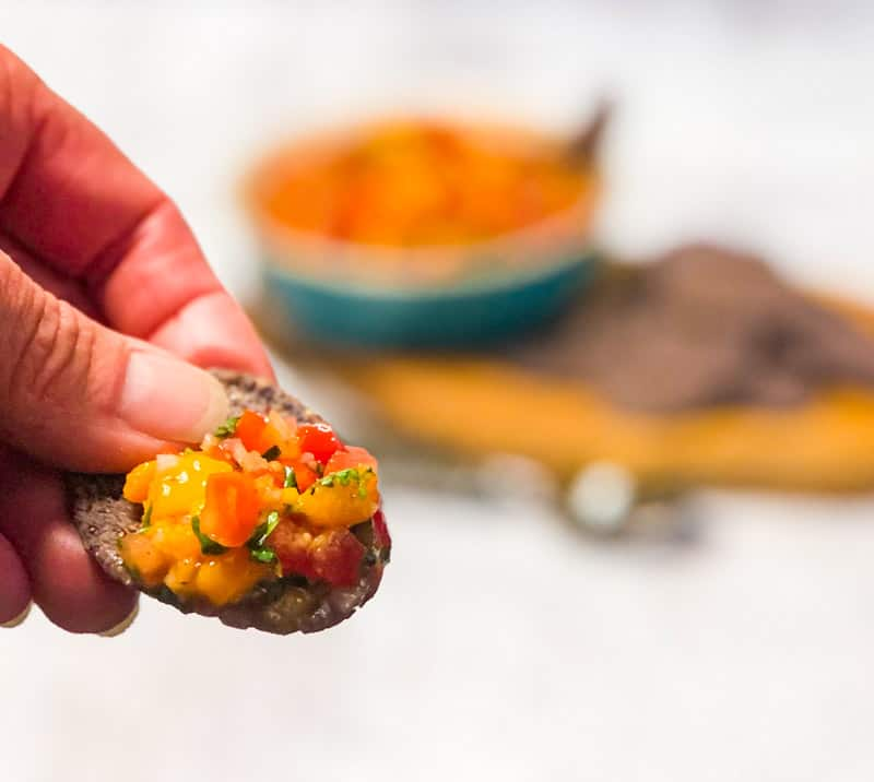 Close up of hand holding a blue corn chip with mango salsa; blurred salsa bowl in background.
