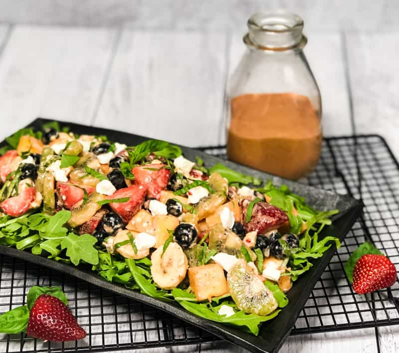 Side shot of Tropical Fruit Salad atop a bed of arugula on a black serving platter on top of a wire rack with bottle of dressing blurred in the background.