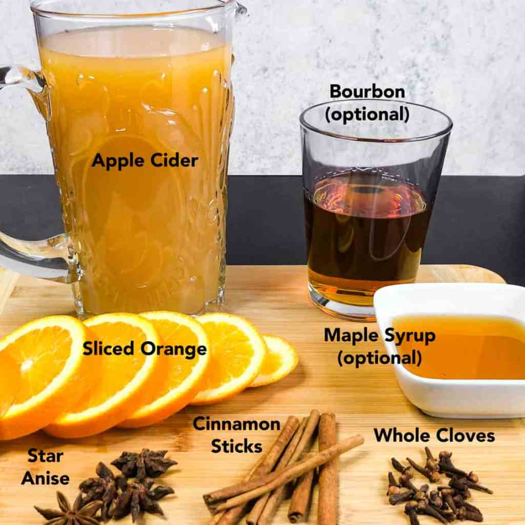 Ingredients for Spiced Apple Cider on a wood cutting board.