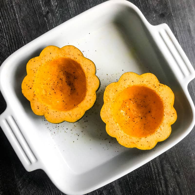 Acorn squash in a white baking dish ready to be roasted.