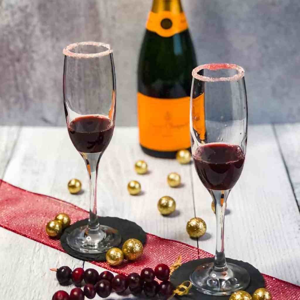 Cranberry juice and spiced simple syrup in sugar rimmed champagne glasses with blurred champagne bottle in background.