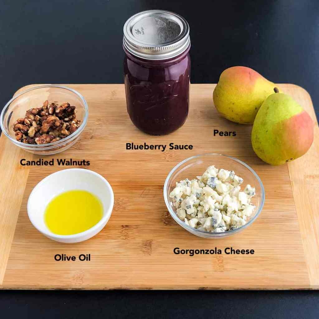 Pears, blueberry sauce, gorgonzola cheese, olive oil, and candied walnuts on a wood cutting board.