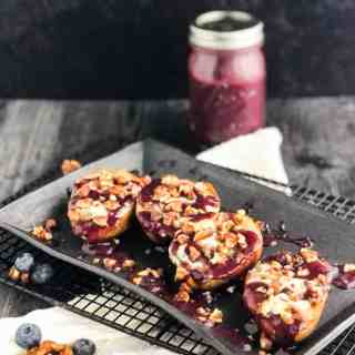 Grilled Pears with Gorgonzola and Candied Walnuts on a black serving platter with jar of blueberry sauce in background.