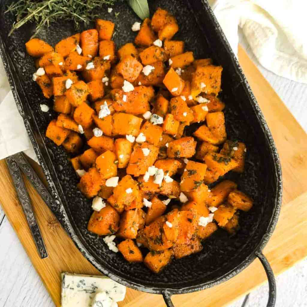 Overhead shot of Savory Roasted Butternut Squash on a metal platter garnished with gorgonzola cheese.