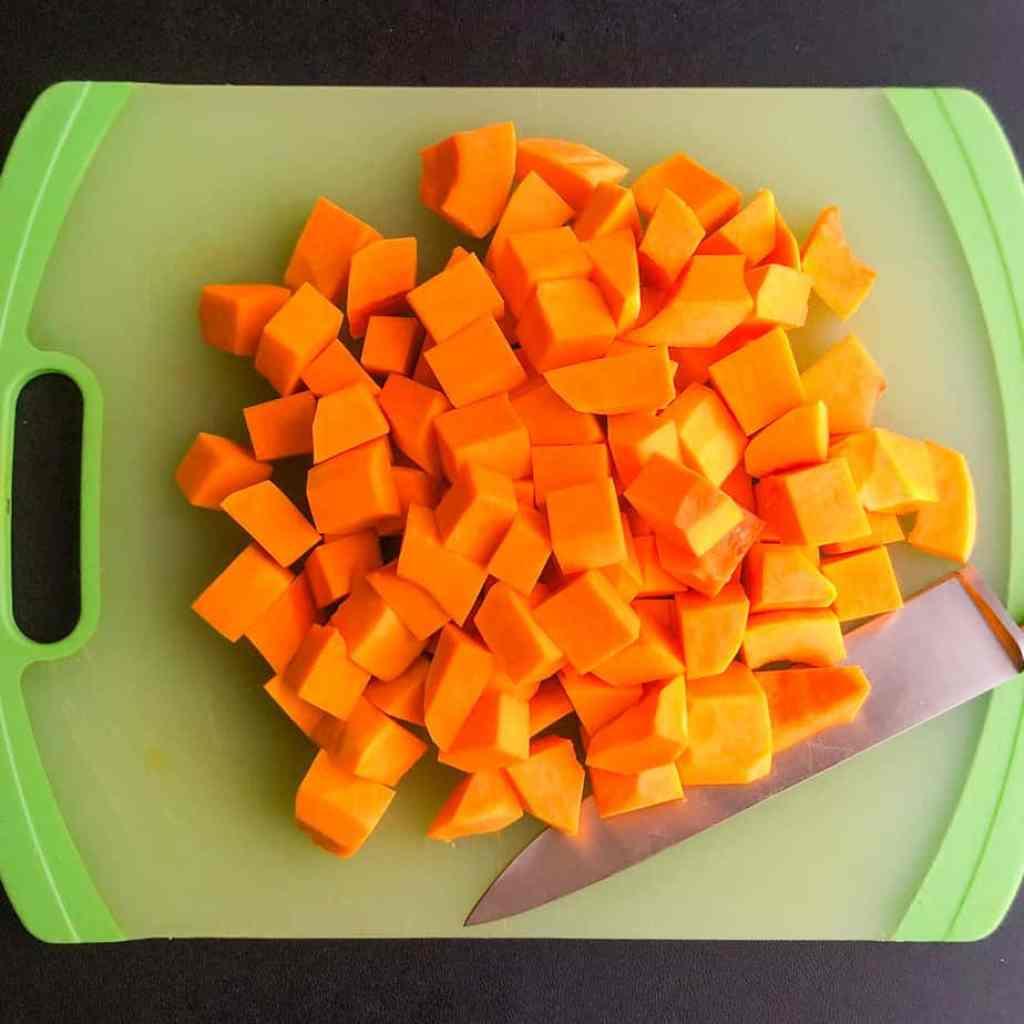 Cut up squash on a green cutting board.