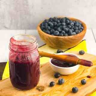 Jar of blueberry sauce in foreground with small ramekin of sauce and bowl of blueberries blurred in the background.