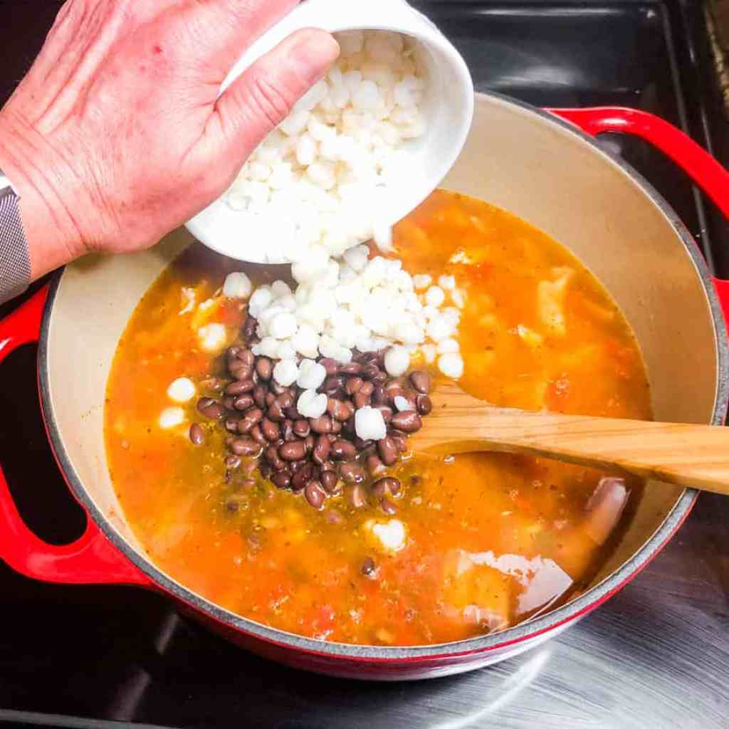 Adding hominy to the Dutch oven.