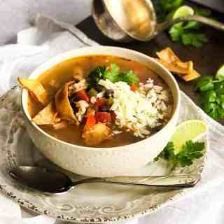 Close up overhead shot of Chicken Tortilla Soup with a ladel and garnishes blurred in the background.