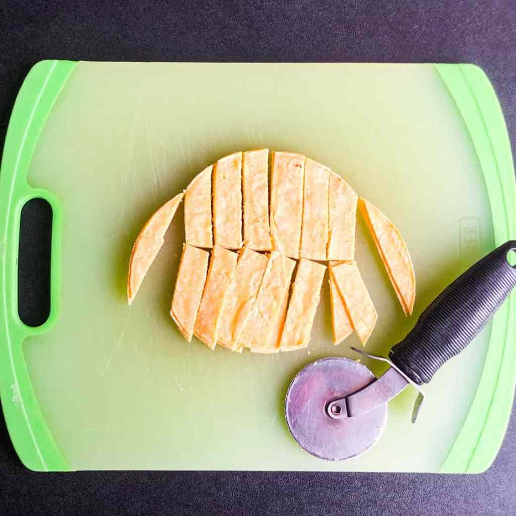 A stack of corn tortillas cut into strips with a pizza slicer on a green cutting board.