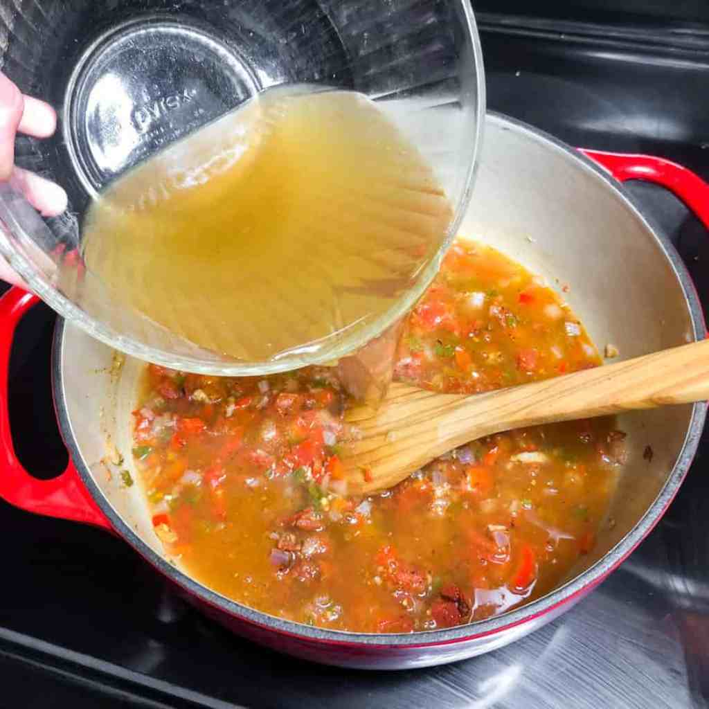 Adding the chicken stock to the Dutch oven.