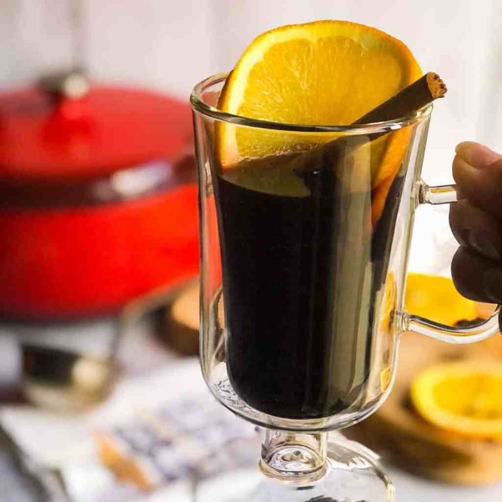 Close up of mulled wine garnished with an orange slice and cinnamaon stick with a red Dutch oven blurred in background.