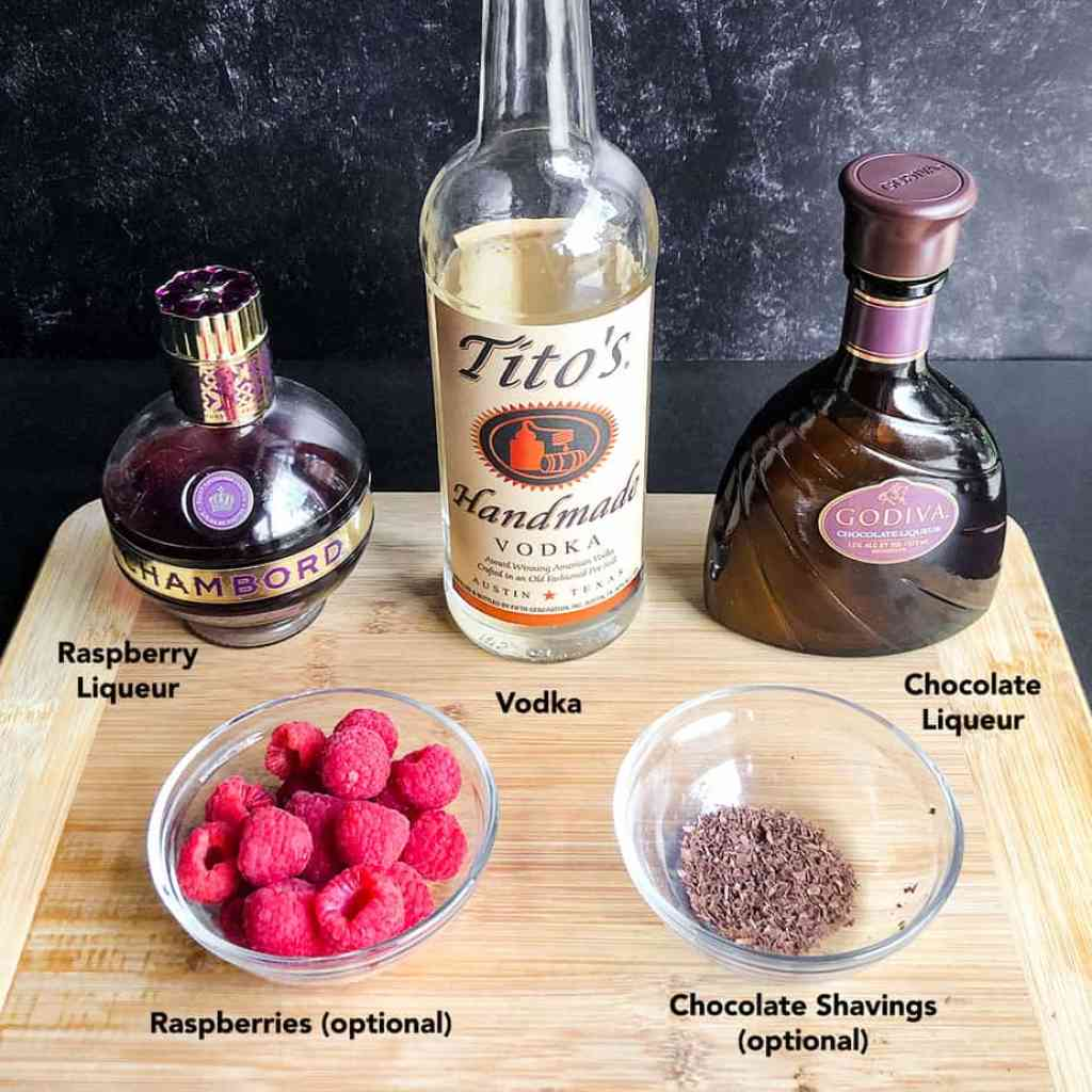 Ingredients for Chocolate Raspberry Martini on a wood cutting board.