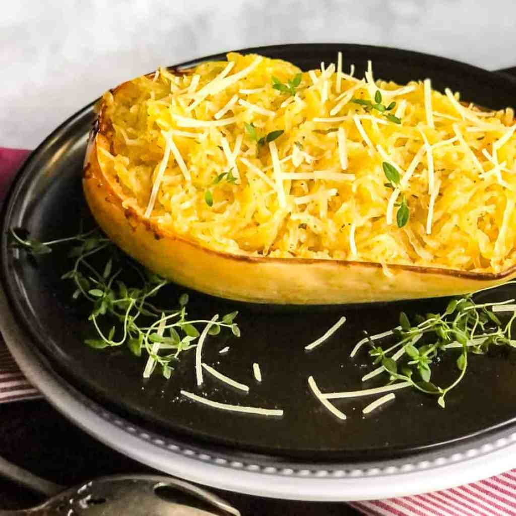 Side shot of Oven Roasted Spaghetti Squash on a black plate garnished with parmesan and fresh thyme.