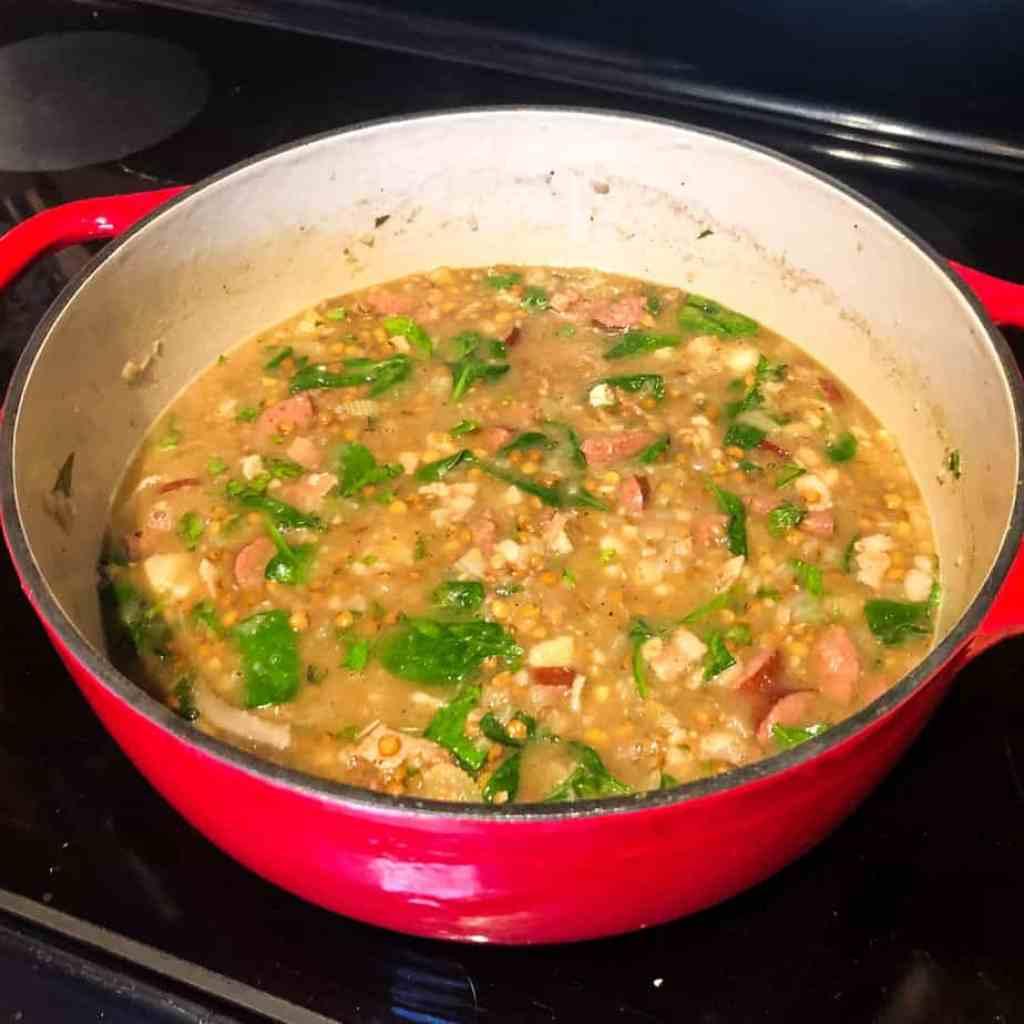 Finished Sausage Lentil Soup in red Dutch oven.