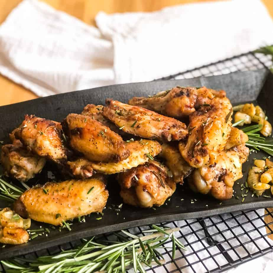 Crispy Smoked Chicken Wings on a black platter garnished with fresh rosemary.