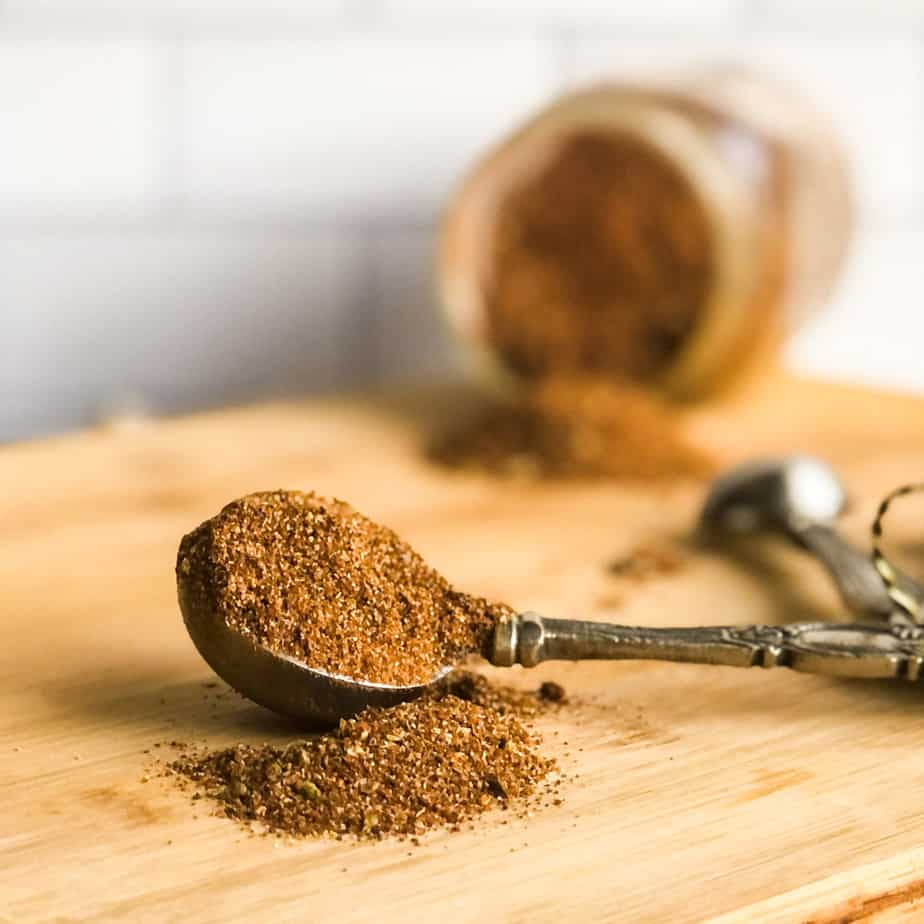 Close up of scoop of taco seasoning on a a tablespoon with jar of seasoning blurred in background.