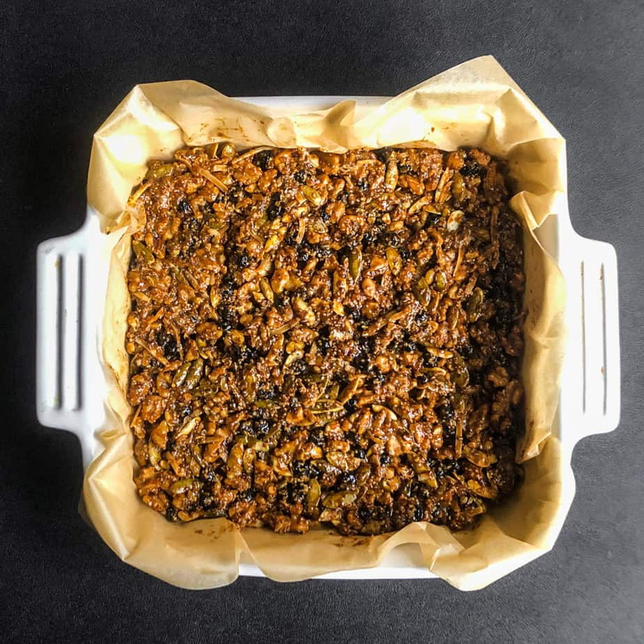 Walnut Bar mixture pressed into a square baking dish lined with parchemnt paper.