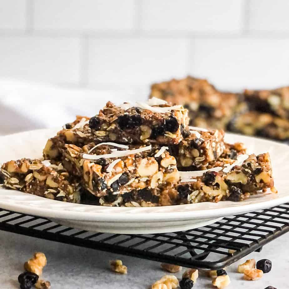 Walnut Bars stacked on a white plate garnished with coconut flakes, walnuts, and dried blueberries.